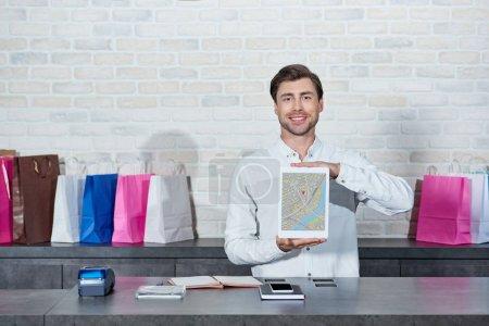Photo pour Beau vendeur jeune tenant une tablette numérique avec la carte sur l'écran et souriant à la caméra à la boutique - image libre de droit
