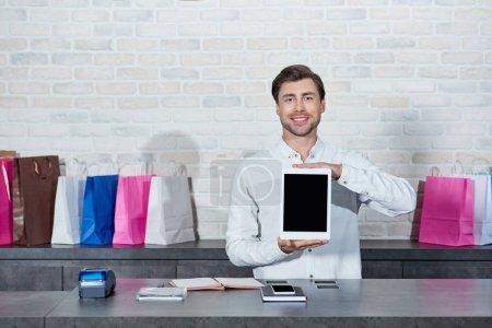 Photo pour Beau vendeur jeune tenant une tablette numérique avec écran blanc et souriant à la caméra à la boutique - image libre de droit
