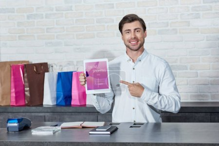 Photo for Handsome young salesman pointing at digital tablet with online shopping application and smiling at camera in store - Royalty Free Image