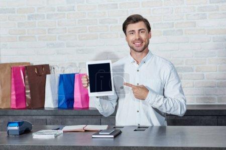 Foto de Guapo joven vendedor señalando tableta digital con pantalla en blanco y sonriendo a la cámara en la tienda - Imagen libre de derechos