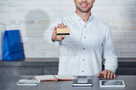cropped shot of smiling young salesman holding credit card in shop