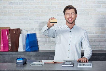 Photo for Handsome young salesman holding credit card and smiling at camera in shop - Royalty Free Image