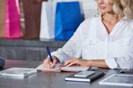 Photo pour Plan recadré de jeune femme écrivant dans un carnet et travaillant dans un magasin - image libre de droit