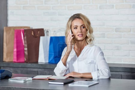 attractive young woman talking by smartphone and looking away while working in shop