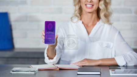 Photo for Cropped shot of smiling young woman holding smartphone with shopping application while working in shop - Royalty Free Image