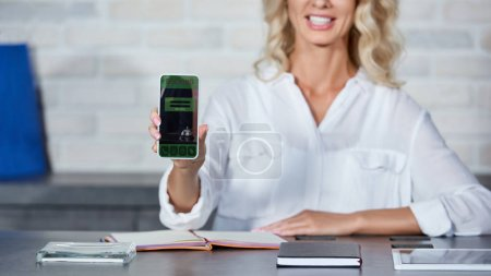 cropped shot of smiling young woman holding smartphone with booking application while working in shop