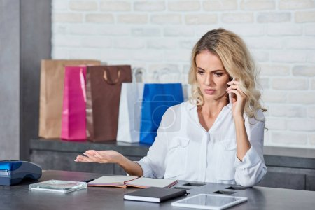Photo for Emotional young woman talking by smartphone while working in shop - Royalty Free Image