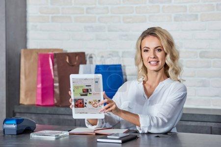Photo pour Belle jeune femme tenant une tablette numérique associé à l'application ebay et souriant à la caméra alors qu'il travaillait dans le magasin - image libre de droit