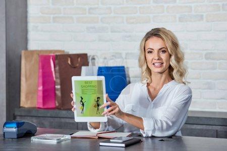 Foto de Hermosa mujer joven con tableta digital con aplicación de compras mejor y sonriendo a cámara mientras trabajaba en la tienda - Imagen libre de derechos