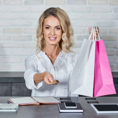 Photo for Smiling young woman holding credit card and shopping bags while working in store - Royalty Free Image