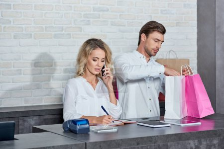 Photo for Young woman talking by smartphone and colleague holding shopping bags in store - Royalty Free Image
