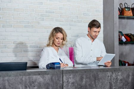 Photo for Young man using digital tablet and woman taking notes while working together in store - Royalty Free Image