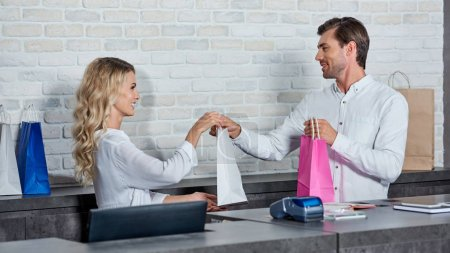Photo for Smiling young woman giving shopping bag to colleague in store - Royalty Free Image