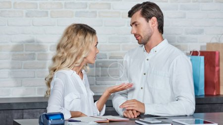 Photo for Young coworkers talking and looking at each other while working together in store - Royalty Free Image