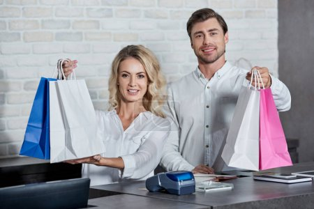 Photo for Happy young shop workers holding paper bags and smiling at camera in store - Royalty Free Image
