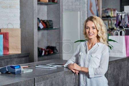 Photo pour Belle jeune femme souriant à la caméra dans le magasin - image libre de droit