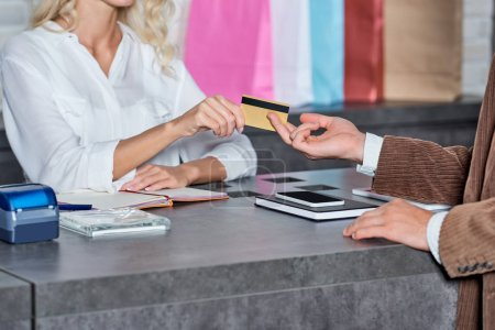 Photo for Cropped shot of customer giving credit card to seller in shop - Royalty Free Image