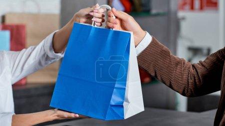 Photo pour Plan recadré du vendeur et de l'acheteur tenant des sacs à provisions en magasin - image libre de droit