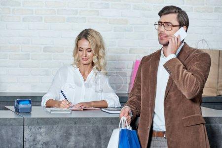 Photo pour Homme souriant tenant des sacs à provisions et parler de smartphone tout en femelle vendeur prenant des notes dans la boutique - image libre de droit