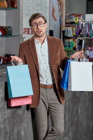 Photo for Uncertain man in eyeglasses holding shopping bags and looking at camera in store - Royalty Free Image