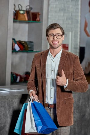 Photo for Happy handsome man with paper bags smiling at camera and showing thumb up in shop - Royalty Free Image