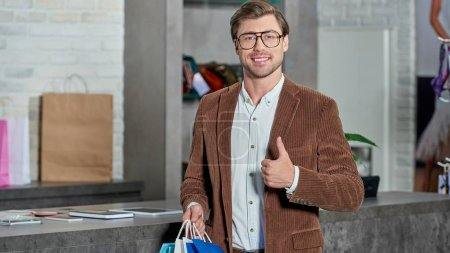 handsome man with shopping bags smiling at camera and showing thumb up in store