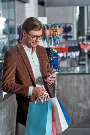 Photo pour Bel homme souriant à lunettes tenant des sacs en papier et en utilisant le smartphone en boutique - image libre de droit
