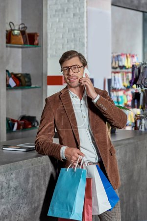 smiling young man in eyeglasses holding shopping bags and talking by smartphone while shopping in mall