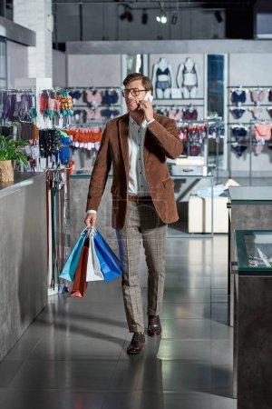 Photo pour Bel homme souriant à lunettes, tenant les sacs en papier et de parler de smartphone en boutique - image libre de droit