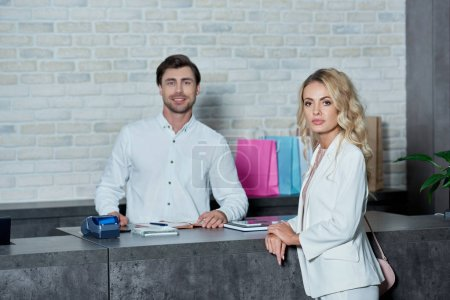 Photo for Beautiful young woman and smiling salesman looking at camera in shop - Royalty Free Image