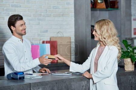 Photo pour Belle jeune cliente donnant carte de crédit au vendeur souriant dans la boutique - image libre de droit