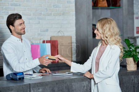 Photo pour Souriant jeune client donnant carte de crédit au vendeur dans le magasin - image libre de droit