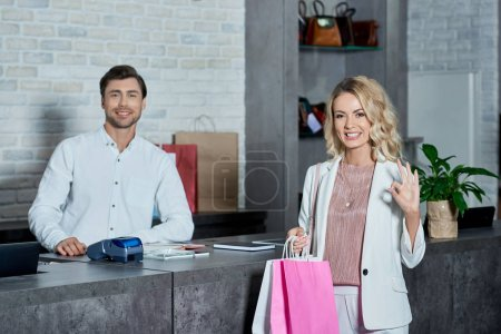 young shop worker smiling at camera and female customer with shopping bags showing ok sign