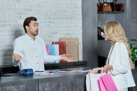 uncertain seller looking at customer showing paper bag in shop