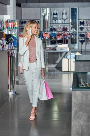 smiling young woman with paper bags talking by smartphone and looking away while shopping in store