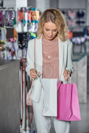 young woman looking into shopping bag in store