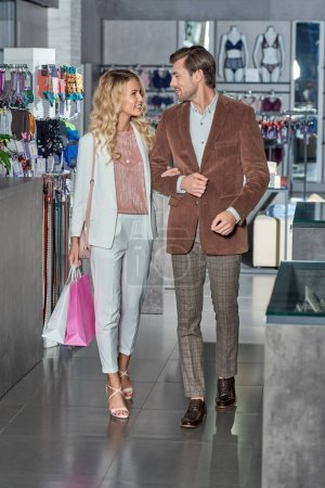 Photo for Stylish young couple with shopping bags smiling each other in boutique - Royalty Free Image