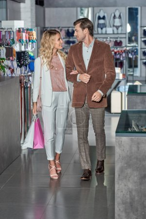 Photo for Stylish couple with shopping bags smiling each other in store - Royalty Free Image