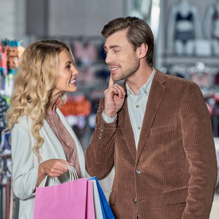 Photo for Attractive young woman with shopping bags able to kiss smiling man in store - Royalty Free Image