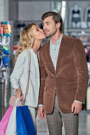 Photo for Young woman holding shopping bags and kissing man in boutique - Royalty Free Image