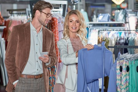 smiling man with smartphone and young woman shopping together in boutique