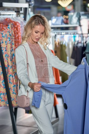 Photo for Young blonde woman choosing stylish clothes in fashion boutique - Royalty Free Image