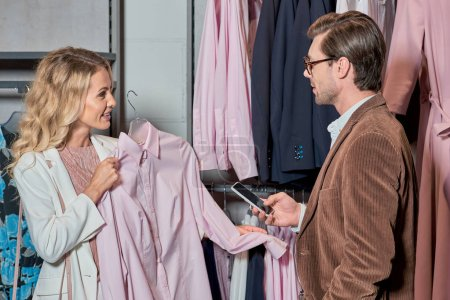 handsome man using smartphone while woman choosing clothes in boutique