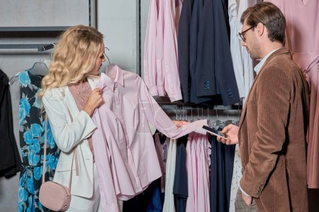 Photo for Young couple choosing fashionable clothes in boutique - Royalty Free Image