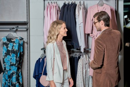 Photo for Smiling young couple choosing fashionable clothes in shop - Royalty Free Image