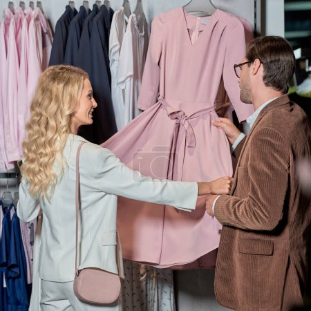Photo for Couple looking at fashionable pink dress in boutique - Royalty Free Image