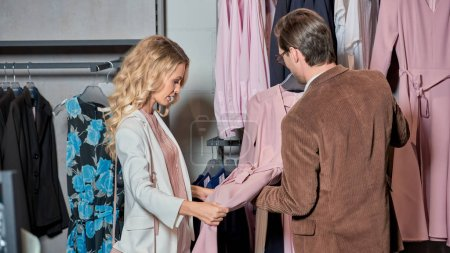 Photo for Stylish couple choosing fashionable clothes in boutique - Royalty Free Image
