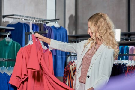 beautiful young woman looking at stylish dress while shopping in store