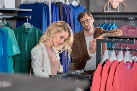 bored man looking at young woman choosing clothes in boutique