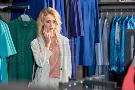 Photo for Young woman looking at fashionable clothes while shopping in boutique - Royalty Free Image